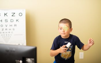Pediatric patient wearing an eye patch on his left eye and playing a Wii game to treat lazy eye