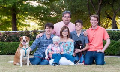 Hawes Family Photo - Mom, Dad, four sons, and a dog sitting outside and smiling. Both parents wearing glasses.